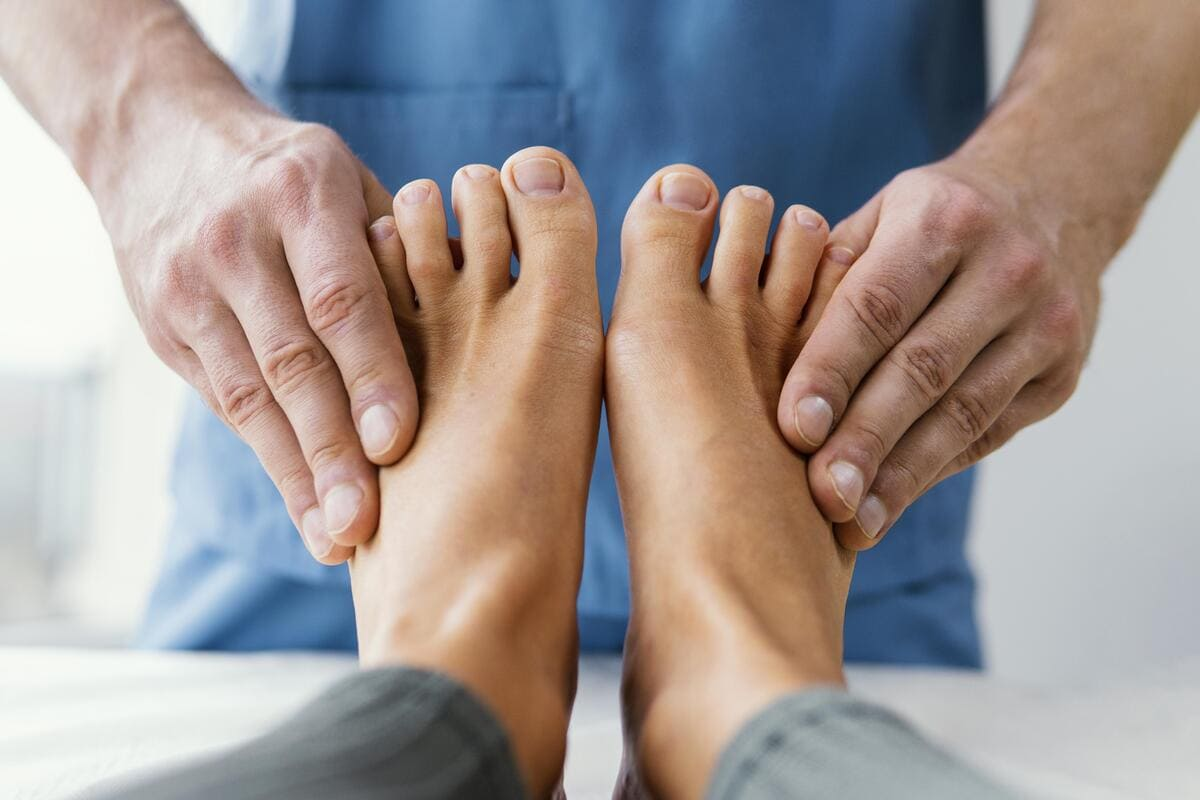 front view of male osteopathic therapist checking female patient s toes 1 1